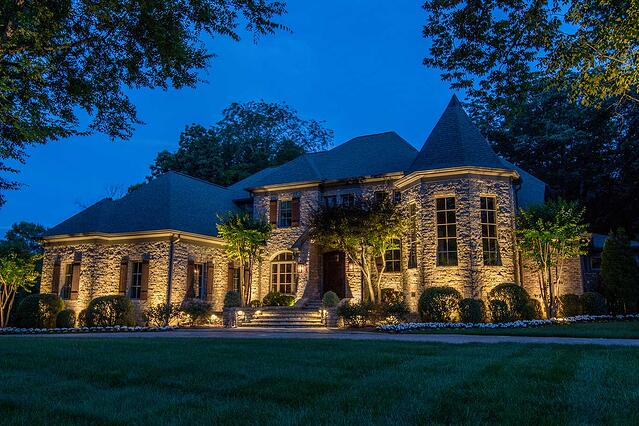Up lighting with grazing effect on home's stone facade