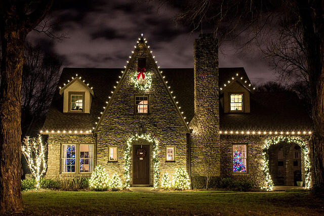 Holiday lights on home with stone facade