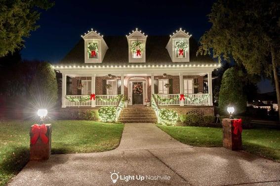 Holiday lighting display with greenery