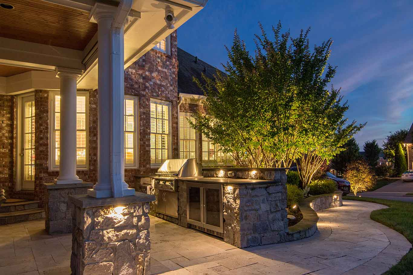 Outdoor lighting on hardscape features of outdoor kitchen area