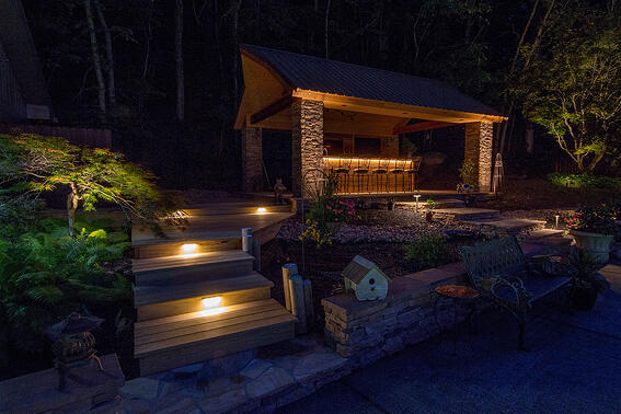 Outdoor lighting on steps and outdoor bar in backyard living area